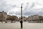 A lone piper plays to an empty square in front of Nelsons Column in Trafalgar Square in London on March 20th, 2020. The centre of London is extremely quiet after the numbers of tourists has plummeted and locals limit their activities due to the Coronavirus crisis.