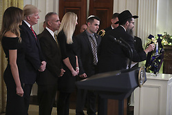 Rabbi Avraham Friedman, right, holds the candle to light the menorah next to President Donald Trump, second left, and first lady Melania Trump, right, Andy Pollack, center left, Julie Phillips, center, and Hunter Pollack, second right, during a Hanukkah reception in the East Room of the White House on December 6, 2018 in Washington, DC. Andy's 18-year-old daughter Meadow Pollack was killed in the Stoneman Douglas High School shooting on February 14, 2018. (Photo by Oliver Contreras/SIPA USA)
