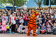 A performer dressed up as Tigger greet the audience during a parade at Walt Disney Co.s Shanghai Disneyland theme park  towards the iconic castle during a trial run ahead of its official opening, in Shanghai, China, on Wednesday, June 8, 2016. The $5.5 billion Shanghai Disneyland is one  of the most profitable Disney ventures in the world and the first theme park on mainland China.