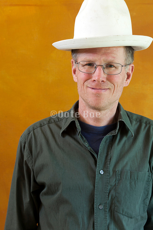 male person with strange smiling expression wearing a white plaster hat