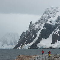 Tourists from a cruise ship stand on the shore of Petermann Island, Antarctica. Behind are mountains and glaciers on the Antarctic Peninsula.