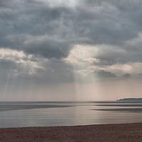Cloud spotlights moves across the still surface of the ocean.