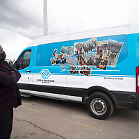 Marisa Hutchinson, director of the Boys and Girls Club of Gallup looks at the 15 passenger van she recently purchased Wednesday afternoon at the Rio West Mall in Gallup. The sides of the van are decorated with kids from the Boys and Girls Club of Gallup.