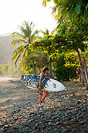 A woman carries her surfboard out of the water in Guanacaste, Costa Rica.