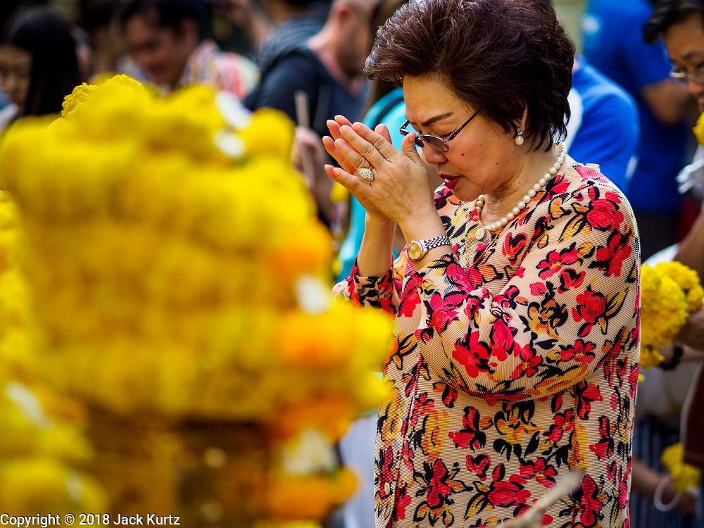 31 DECEMBER 2018 - BANGKOK, THAILAND: A woman prays after leaving an offering of marigolds at the Erawan Shrine in Bangkok. The shrine was packed with tourists and Thais praying and making merit on New Year's Eve. Many Thais go to temples to meditate and pray on New Year's Eve.   PHOTO BY JACK KURTZ