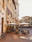 A restaurant and cafe early in the morning on Piazza della Cisterna in San Gimignano, a UNESCO Heritage site, Tuscany, Italy