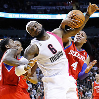 21 January 2012: Miami Heat small forward LeBron James (6) is fouled by Philadelphia Sixers point guard Lou Williams (23) and Philadelphia Sixers center Tony Battie (4) during the Miami Heat 113-92 victory over the Philadelphia Sixers at the AmericanAirlines Arena, Miami, Florida, USA.