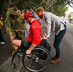 The Duke of Sussex helps a competitor with his wheelchair at the 2018 Invictus Games in Sydney, Australia.
