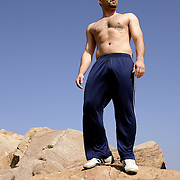 ACTON, CALIFORNIA, March 25, 2007: Shervin Ilbeig stands on rocks with no shirt on at Vazquez Rocks in Acton, California. (Photograph by Todd Bigelow/Aurora)