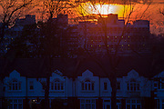 Setting sun between layers of cloud over inner-city south London rooftops. As the sun sinks inn the winter sky, over the inner-city of Britain's capital, we see a variety of eras in the architecture of urban housing: From Ewardian period in the foreground to the tower blocks from the 60s in the distance. A warm glow of light flares from the camera lens to give an almost cosy feel to the landscape while giving a sense of raw cold on this April evening.