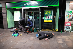 © Licensed to London News Pictures . 27/10/2018. Manchester, UK. A man , believed to be under the influence of Spice , lies on the ground outside a branch of Paddypower , in Piccadilly Gardens in Manchester City Centre as revellers on a night out , many in fancy dress , enjoy the weekend before Halloween . Photo credit: Joel Goodman/LNP
