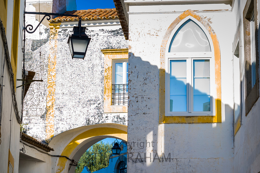 Typical white and yellow houses and buildings and lantern in Evora, Portugal