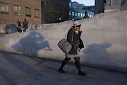 A woman adjusts her hat on the south side of London Bridge in Southwark, central London