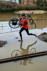 © Licensed to London News Pictures. 03/03/2014. BRISTOL, UK A man makes his way with a bike through a flooded section of the cycle path and harbour railway line by the river Avon and Cumberland Road in Bristol during this morning's high tide. Photo credit : Artur Lesniak/LNP