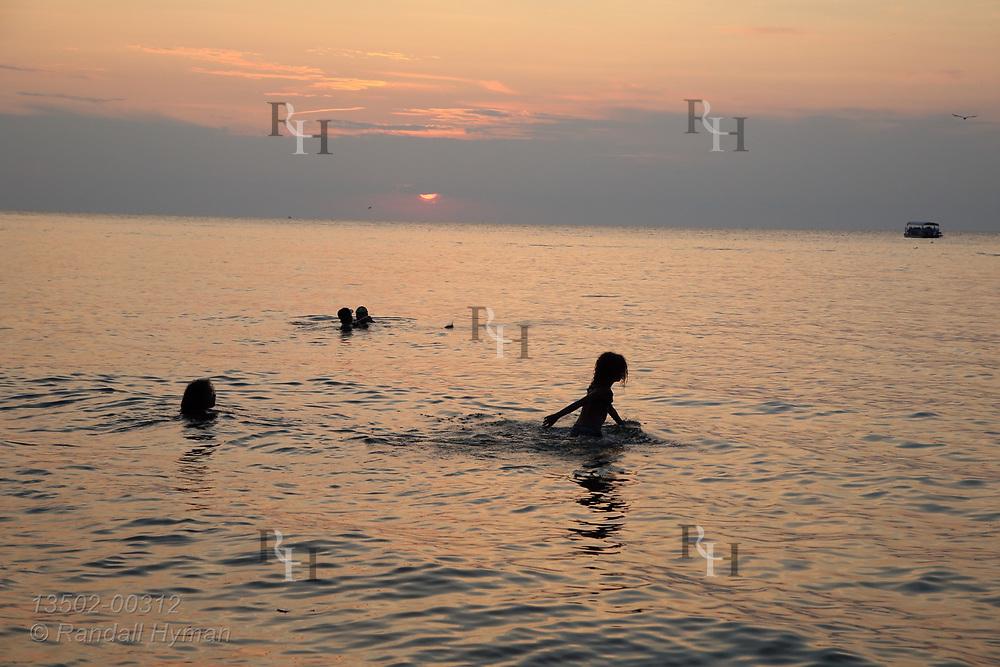 Kids swim in Lake Erie at sunset at Vermilion, OH.