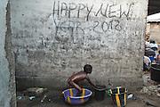 A girl bathes in a plastic container in the West Point slum in Monrovia, Montserrado county, Liberia on Monday April 2, 2012.