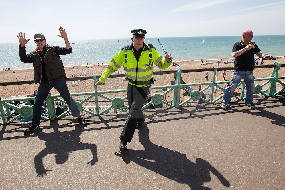© Licensed to London News Pictures . 21/04/2013 . Brighton , UK . A policeman with his baton raised intervenes to separate protesters who are fighting on the seafront . Nationalist group March for England hold a march along Brighton seafront today (Sunday 21st April) . The group was supported by supporters of the English Defence League and opposed by anti fascist and left wing groups . The annual march takes place close to St George's Day and frequently results in scuffles and violence between opposing groups and police . Photo credit : Joel Goodman/LNP