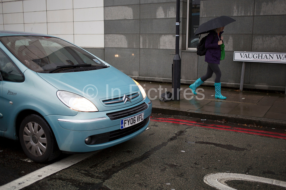 Wellington boots match a passing car on a wet rainy day in Wapping, East End of London, UK.