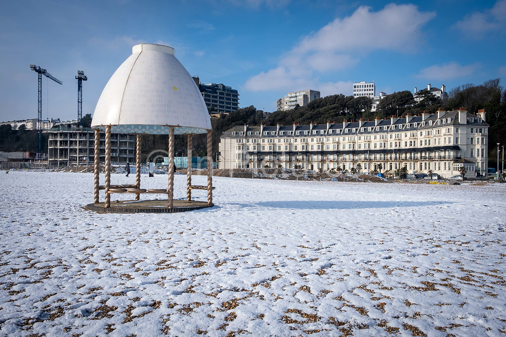 Snow on the beach at Folkestone seafront where the Jelly Mould Pavilion sits on the 11th of February 2021, Folkestone, United Kingdom. Designed by Turner Prize winner Lubaina Himid MBE made as part of the 2017 Folkestone Triennial. Folkestone, Kent. Lubaina Himid created a Jelly Mould Pavilion on Folkestone's sea front, on the former 'Rotunda' site of the town's fun fair, Lido and amusement park where the sugar of candy floss and toffee apples fuelled summer visitors. The pavilion's colourful decoration in the artist's signature patterning will serve as a reminder of the lost amusement park, as well as providing a beautiful shelter at the edge of the town to rest, look out to sea, and think about the role of sugar in Britain's history. Folkestone, Kent.