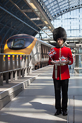 © licensed to London News Pictures. London, UK 24/07/2012. A soldier with tea pots and union flag waiting to welcome French and Belgium athletes on an Eurostar platform in St.Pancras Station, London. Photo credit: Tolga Akmen/LNP