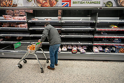 © Licensed to London News Pictures. 21/12/2020. London, UK. A shopper looks at empty shelves of Christmas turkeys and chicken in the meat aisles this afternoon in an Asda in London. Chaotic scenes at Asda in Wandsworth, South West London as a huge rush of shoppers descended on the store causing long queues in the aisles after news that French customs blocked freight from leaving Dover to France after a Covid-19 mutation caused a rapid increase of infection throughout the capital and South East of England. Last week Prime Minister Boris Johnson put London and parts of the South East into Tier 4 lockdown after the new Covid-19 mutation was discovered. Photo credit: Alex Lentati/LNP