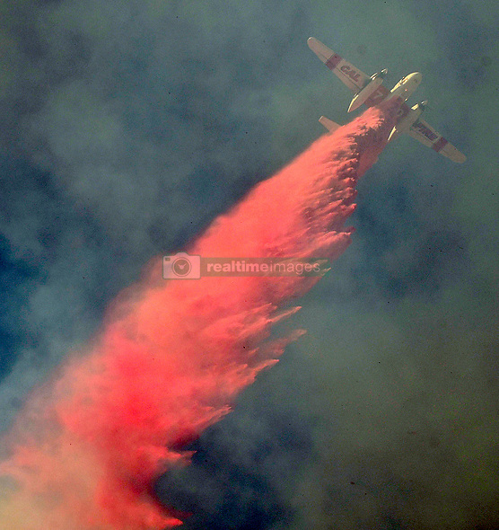 November 11, 2018 - West Hills, California, U.S. - Air tanker makes a drop from above to save home from flair up winds of the Woolsey fire Sunday Morning. The fire burn behind homes along Valley Cir Blvd. and Stagg St. and was stopped within a few hours. (Credit Image: © Gene Blevins/ZUMA Wire)