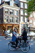 Young people on bicycles chatting in the Nine Streets district of  Amsterdam, Holland