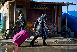 © Licensed to London News Pictures. 23/10/2016. Calais, France. A young woman migrant drags her suitcase through the 'Jungle' camp in Calais ahead of it's demolition, which is scheduled for this week. French authorities have given an eviction order to thousands of refugees and migrants living at the makeshift living area of the French coast. Photo credit: Ben Cawthra/LNP