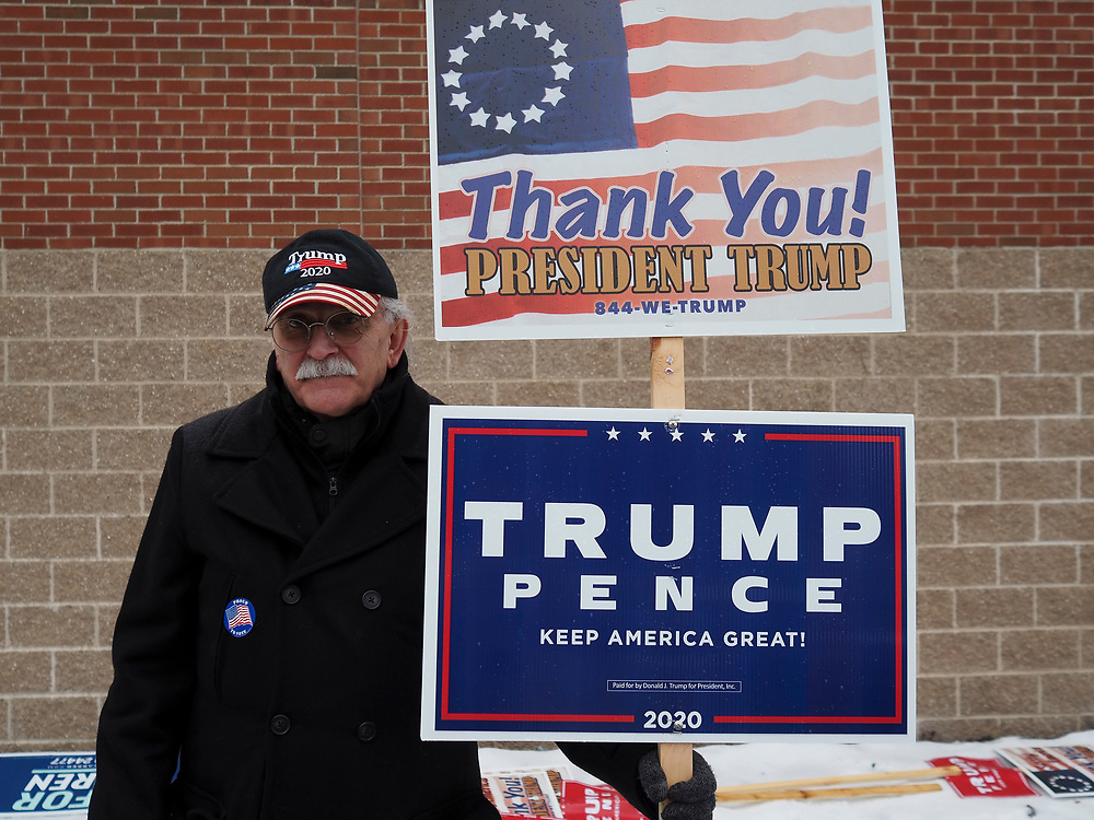A President Trump supporter stands outside a New Hampshire polling site.