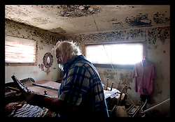 4th Oct, 2005. Hurricane Katrina aftermath, New Orleans, Louisiana. Tinsley Sammons retrieves the little he can from his home severly mouldy home in the Arabi neighbourhood after the devastating floods which filled his house to the ceiling with water and toxic mud.