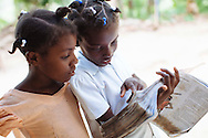 Natacha Etienne (right), 12, reads a Bible story book with one of her cousins outside the small, two-room home she shares with her parents and siblings in Loncy village, Haiti.