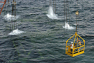 KEVIN BARTRAM/The Daily News.Workers hang from a crane over the Gulf of Mexico about 100 miles south of Galveston as an abandoned offshore platform is lowered on Tuesday, June 28, 2005. Air trapped in the legs of The El Paso Corporation platform bubbled to the surface as the platform was lowered into about 200 feet of water to form an artificial reef.