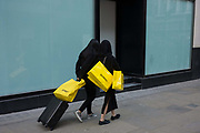 Two women Selfridges shoppers are seen from behind as they walk along Old Bond Street, central London. Making their way past the blank window of a temporarily-closed shop, their yellow bags are prominent against their black clothing and plain background, These two lady consumers carry their purchases from one of the capital's most famous retail brands. Selfridges was founded by Harry Gordon Selfridge and the flagship store in London's Oxford Street is the second largest shop in the UK (after Harrods) and was opened on 15 March 1909.