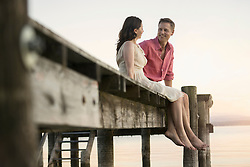Mature couple looking at each other and smiling on pier, Bavaria, Germany