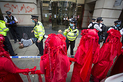©️ Licensed to London News Pictures. 04/09/2020. London, Extinction Rebellion (XR) activists group glued themselves outside Department for Transport entrance, meanwhile other activists pelted red colour the building of Department for Transport's main entrance in Horseferry Road, and some others glued themselves outside DPT in central London. XR plan to disrupt areas of central London with actions planned over the next two weeks, until MP's back the Climate and Ecological Emergency Bill and prepare for crisis with a National Citizens' Assembly. Photo credit: Marcin Nowak/LNP