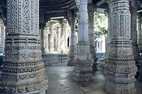 jain architecture: jainism temple in Ranakpur, Rajasthan, India. Glimpse trough marbre pillars of the adinatha jainism temple, that has 1444 marble pillars. Picture with wide depth of field. On foreground pillars in shadow. On background enlightened pillars.Calm mood inspiring meditation.