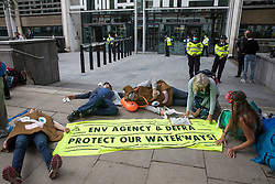 London, UK. 5th August. 2021. Extinction Rebellion activists stage a die-in outside the Department for Environment, Food and Rural Affairs (Defra) in protest against the pollution of the UK's waterways. The activists were highlighting pollution of rivers by water companies and farms and the failure of the Environment Agency and Defra to protect waterways and to prosecute offenders.