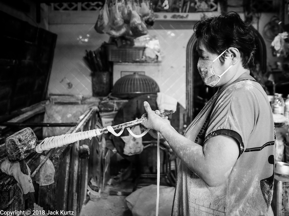 """29 DECEMBER 2018 - BANGKOK, THAILAND: A woman makes longevity noodles in her family shophouse. The family has been making traditional """"mee sua"""" noodles, also called """"longevity noodles"""" for three generations in their home in central Bangkok. They use a recipe brought to Thailand from China. Longevity noodles are thought to contribute to a long and healthy life and  are served on special occasions, especially Chinese New Year, which is February 4, 2019. These noodles were being made for Chinese New Year.   PHOTO BY JACK KURTZ"""