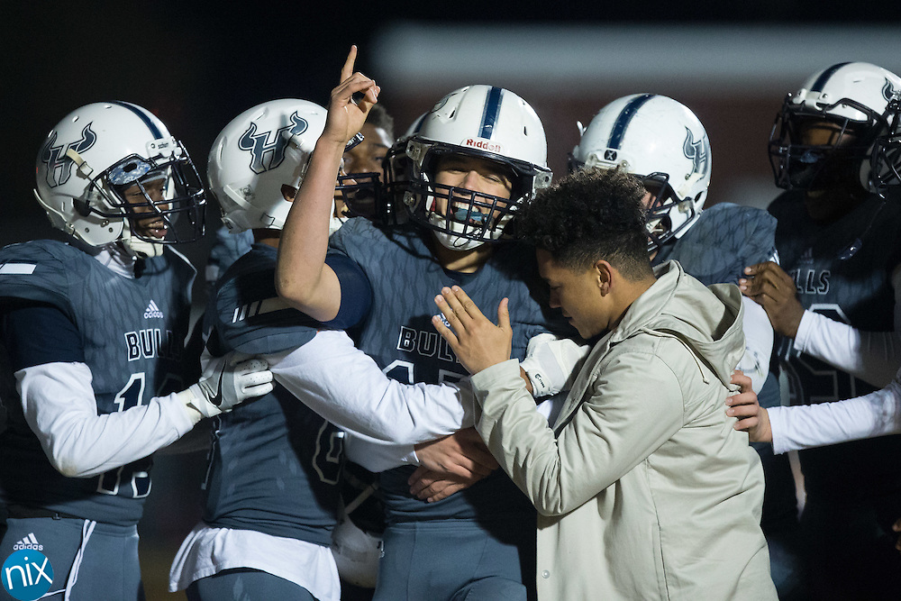 Hickory Ridge Ragin' Bulls quarterback Trevor Shue (15) is mobbed after scoring the winning touchdown against the Marvin Ridge Mavericks in the third round of the NCHSAA 3A playoffs at Hickory Ridge High School on December 2, 2016 in Harrisburg, North Carolina.  The Ragin' Bulls defeated the Mavericks 55-49 in 4 overtimes.  (Brian Westerholt/Special to the Independent Tribune)