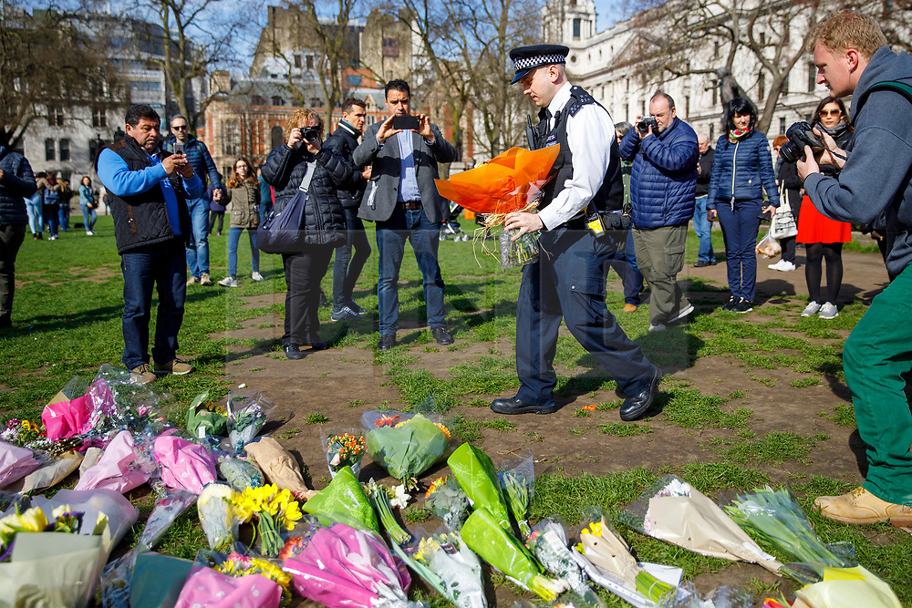 © Licensed to London News Pictures. 25/03/2017. London, UK. A police officer puts down flowers to pay his respects to the victims of Westminster terror attack in Parliament Square, London on 25 March 2017. Photo credit: Tolga Akmen/LNP