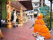 """05 JULY 2011 - BANGKOK, THAILAND:     A wrapped Buddha statue and other Buddha statues for sale on Bamrung Muang Street in Bangkok. Buddha statues are wrapped in saffron cloth before they moved, either from the factory or the store. Thanon Bamrung Muang (Thanon is Thai for Road or Street) is Bangkok's """"Street of Many Buddhas."""" Like many ancient cities, Bangkok was once a city of artisan's neighborhoods and Bamrung Muang Road, near Bangkok's present day city hall, was once the street where all the country's Buddha statues were made. Now they made in factories on the edge of Bangkok, but Bamrung Muang Road is still where the statues are sold. Once an elephant trail, it was one of the first streets paved in Bangkok, it is the largest center of Buddhist supplies in Thailand. Not just statues but also monk's robes, candles, alms bowls, and pre-configured alms baskets are for sale along both sides of the street.      PHOTO BY JACK KURTZ"""