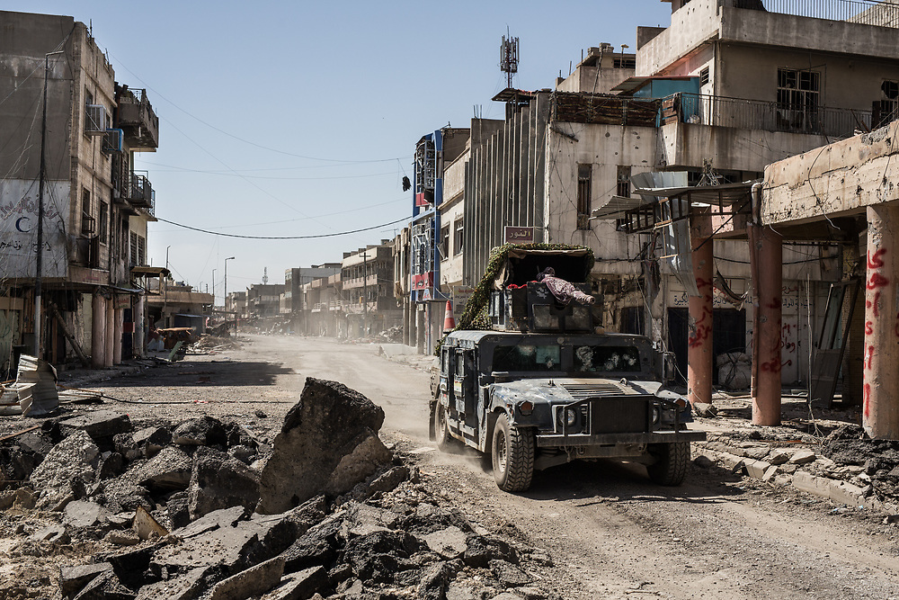 A humvee of Iraqi Federal Police forces drives through a destroyed street near the frontline in West Mosul, Iraq. <br /> <br /> イラク連邦警察軍の装甲車両が、前線近くの破壊された街中を駆け向けていく。イラク、モスル西部、2017年4月撮影。