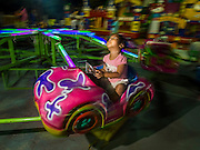 """07 MARCH 2015 - NAKHON CHAI SI, NAKHON PATHOM, THAILAND: A child on a merry-go-round on the midway at the Wat Bang Phra tattoo festival. Wat Bang Phra is the best known """"Sak Yant"""" tattoo temple in Thailand. It's located in Nakhon Pathom province, about 40 miles from Bangkok. The tattoos are given with hollow stainless steel needles and are thought to possess magical powers of protection. The tattoos, which are given by Buddhist monks, are popular with soldiers, policeman and gangsters, people who generally live in harm's way. The tattoo must be activated to remain powerful and the annual Wai Khru Ceremony (tattoo festival) at the temple draws thousands of devotees who come to the temple to activate or renew the tattoos. People go into trance like states and then assume the personality of their tattoo, so people with tiger tattoos assume the personality of a tiger, people with monkey tattoos take on the personality of a monkey and so on. In recent years the tattoo festival has become popular with tourists who make the trip to Nakorn Pathom province to see a side of """"exotic"""" Thailand.   PHOTO BY JACK KURTZ"""