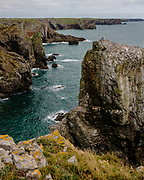 CASTLEMARTIN, WALES - 13 SEPTEMBER 2020: The Green Bridge of Wales, Stack Rocks and Saint Govan's Chapel on the Pembrokeshire coast.