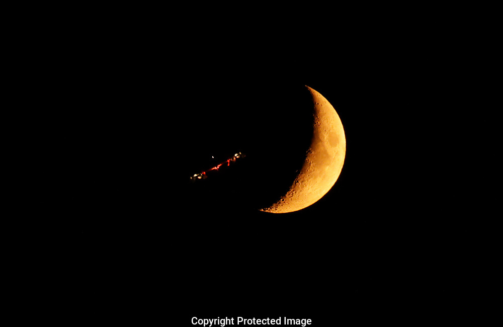 Red crescent moon caused by forest fires in the western states and British Columbia seen from Tacoma, Wash. as a plane from Joint Base Lewis-McChord flies past, Wednesday, Aug. 15, 2018. (Photo/John Froschauer)