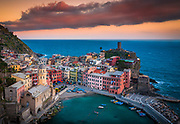 "Vernazza is a town and comune located in the province of La Spezia, Liguria, northwestern Italy. It is one of the five towns that make up the Cinque Terre region. Vernazza is the fourth town heading north, has no car traffic, and remains one of the truest ""fishing villages"" on the Italian Riviera. Vernazza's name is derived from the Latin adjective verna meaning ""native"" and the aptly named indigenous wine, vernaccia (""local"" or ""ours""), helped give birth to the village's moniker. First records recognizing Vernazza as a fortified town date back to the year 1080. Referred to as an active maritime base of the Obertenghi, a family of Italian nobility, it was a likely point of departure for naval forces in defence of pirates. Over the next two centuries, Vernazza was vital in Genova's conquest of Liguria, providing port, fleet, and soldiers. In 1209, the approximately 90 most powerful families of Vernazza pledged their allegiance to the republic of Genova.In 1997, the Cinque Terre was recognized as a World Heritage Site by UNESCO and in 1999 the National Park of the Cinque Terre was born. Today the main source of revenue for Vernazza is tourism. However, as a testimony to the strength of centuries-old tradition, fishing, wine and olive oil production still continue to take place."