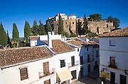 Defensive walls of the old city viewed over historic buildings near Puerta de Carlos V, Ronda, Spain