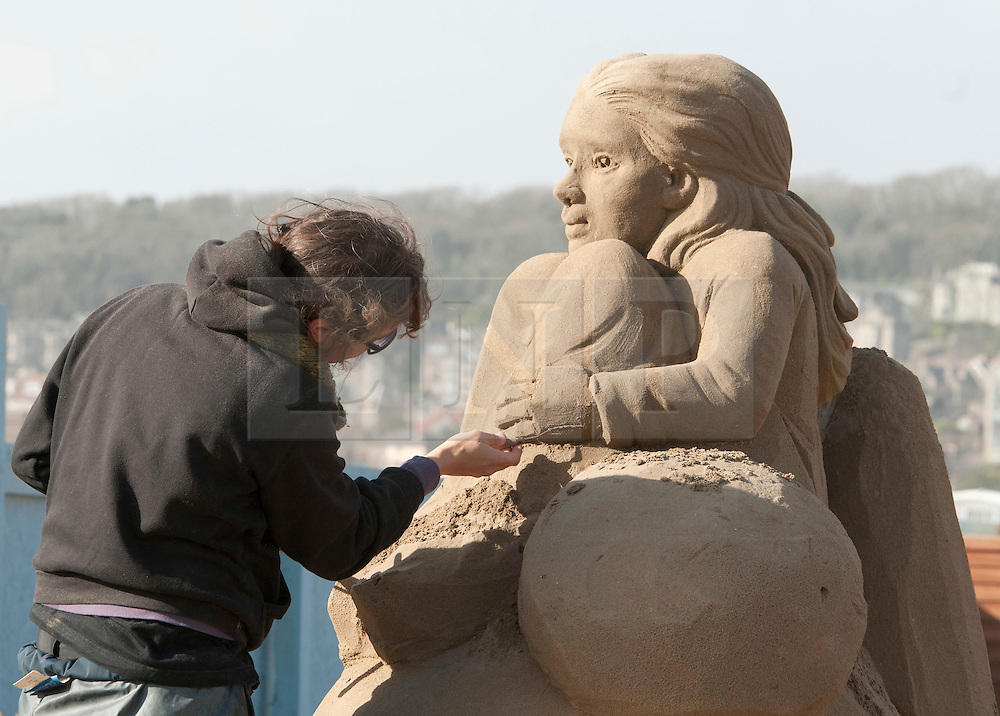 © Licensed to London News Pictures.  31/03/2015. Weston-super-Mare, North Somerset, UK.  Sand sculptors put the finishing touches to their work at the Sand Sculpture Festival on Weston-super-Mare beach.   This is the 10th year of sand sculptures in Weston and the theme is a nostalgic visit through the last 10 years of the festival, which is open daily from the 3rd April to 27th September 2015. Photo credit : Simon Chapman/LNP