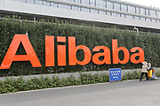 A employee walks past the Alibaba sign at the company's head quarters in Hangzhou , China on 11 November 2013. Alibaba, the parent company of T Mall, recorded $5.78 billion of sales during this Chinese version of Black Friday in 2013, as people in China increasingly log on to their computers to shop.