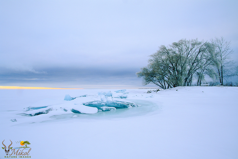 Lonely, cloudy, cold winter evening with broken ice from frozen lake. Empty Park bench